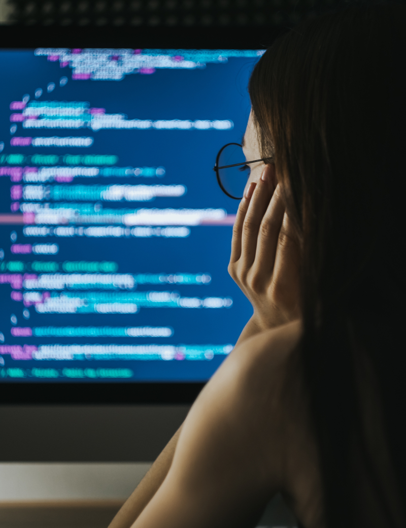 Female software engineer looking at code on computer screen